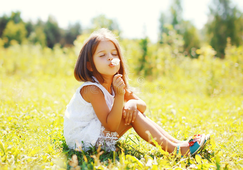 Gulligt liten flickabarn som blåser maskrosblomman i solig sommar arkivbild