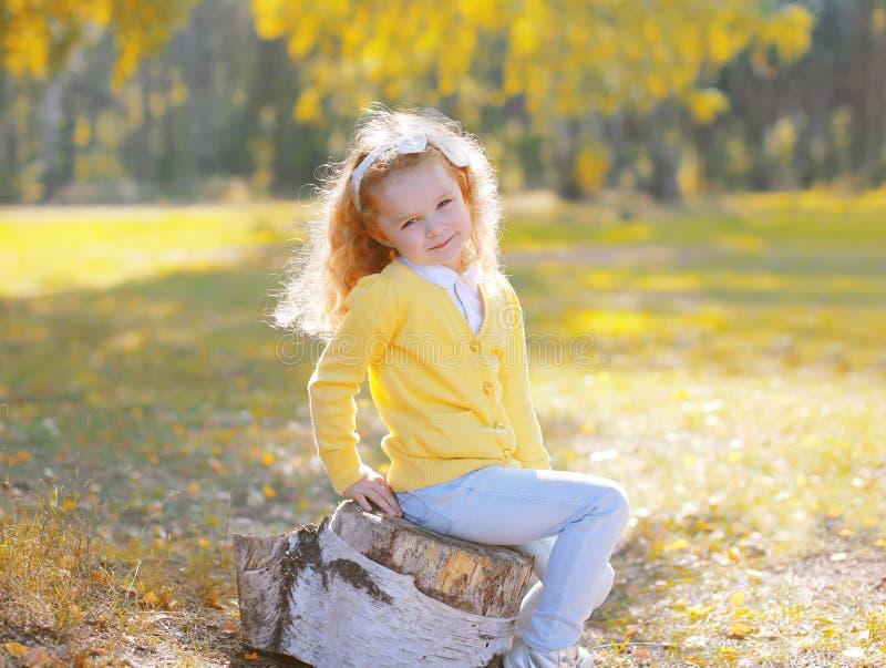 Gulligt liten flickabarnsammanträde på stubbe i solig höst royaltyfria bilder