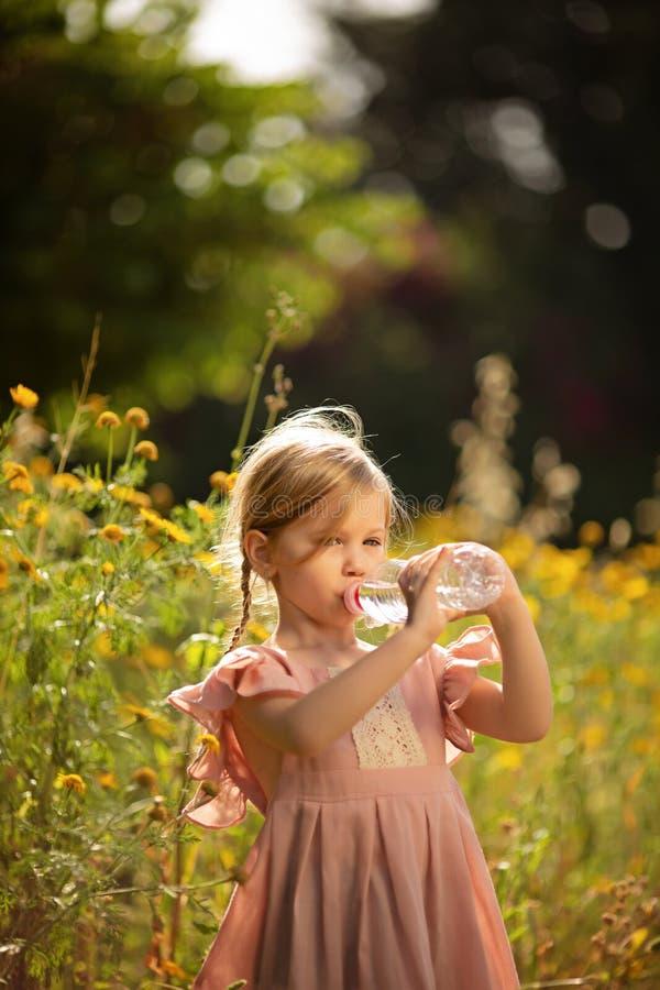 Gulligt liten flickadricksvatten i en sommarträdgård arkivfoton