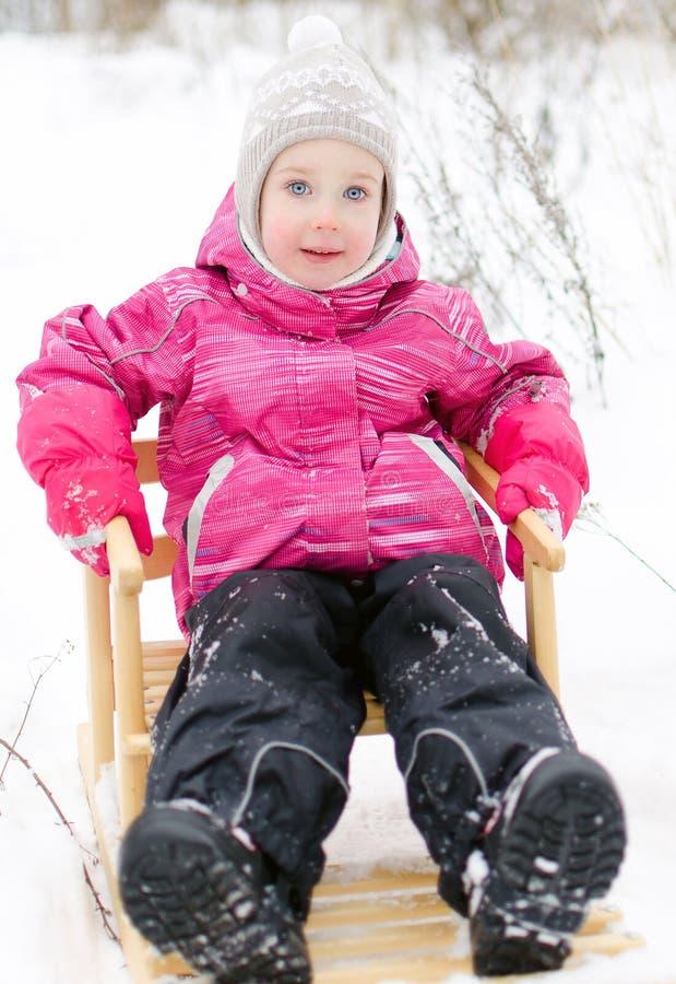 Gulligt liten flickasammanträde i sled fotografering för bildbyråer