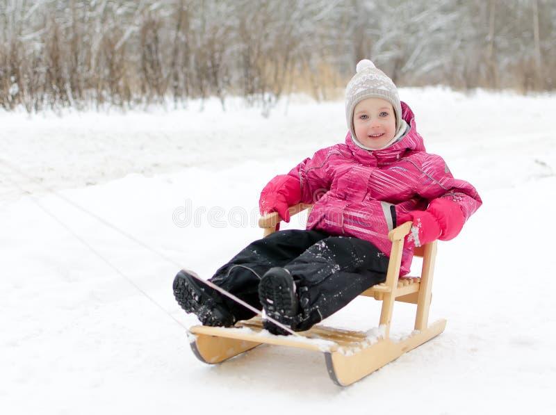 Gulligt liten flickasammanträde i sled royaltyfria bilder