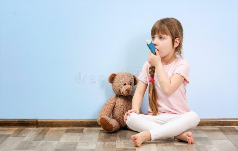 Gulligt liten flickasammanträde på golv, medan genom att använda inhalatorn royaltyfri bild