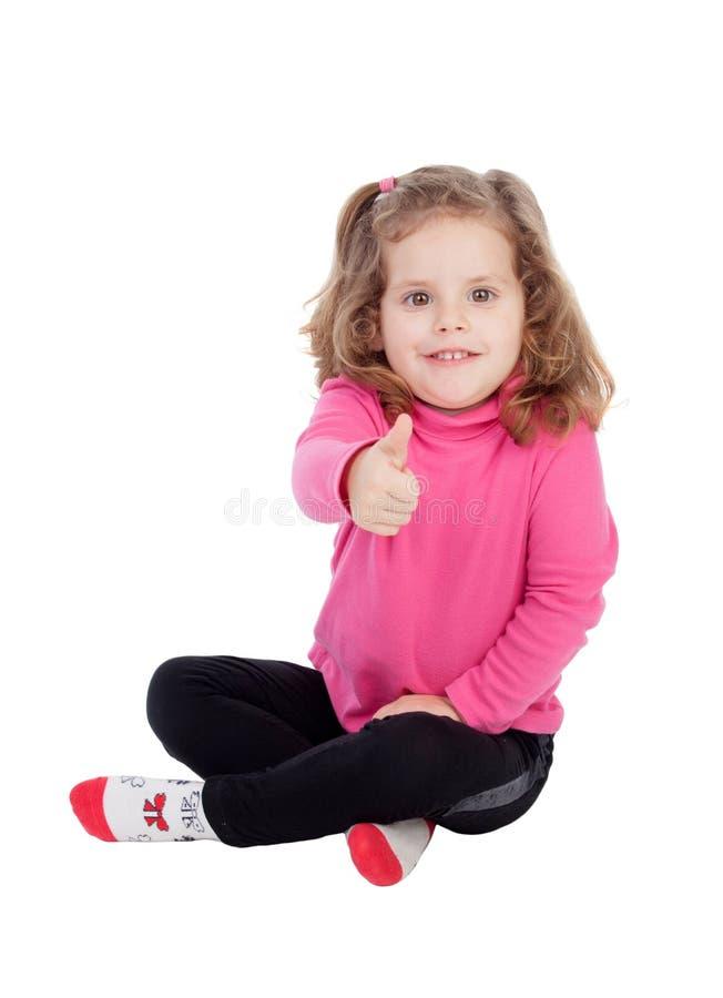 Gulligt liten flickasammanträde på golvet som Ok säger royaltyfri fotografi