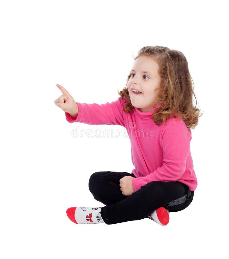 Gulligt liten flickasammanträde på golvet som pekar något med th royaltyfri foto