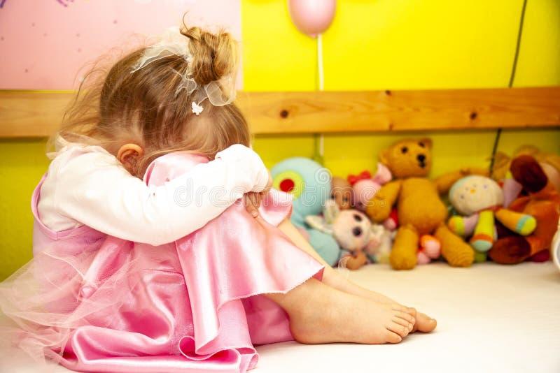 Gulligt liten flickasammanträde på mycket olycklig säng royaltyfri foto
