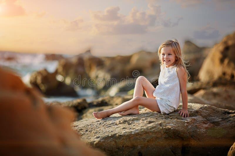 Gulligt liten flickasammanträde på stranden på solnedgången arkivfoto
