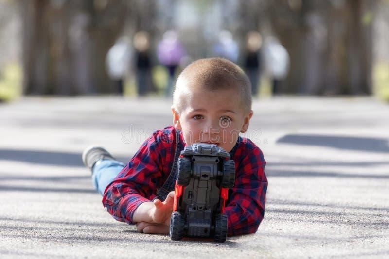 Gulligt litet barn, blond litet barnpojke som spelar utomhus att ligga på gatan royaltyfri fotografi