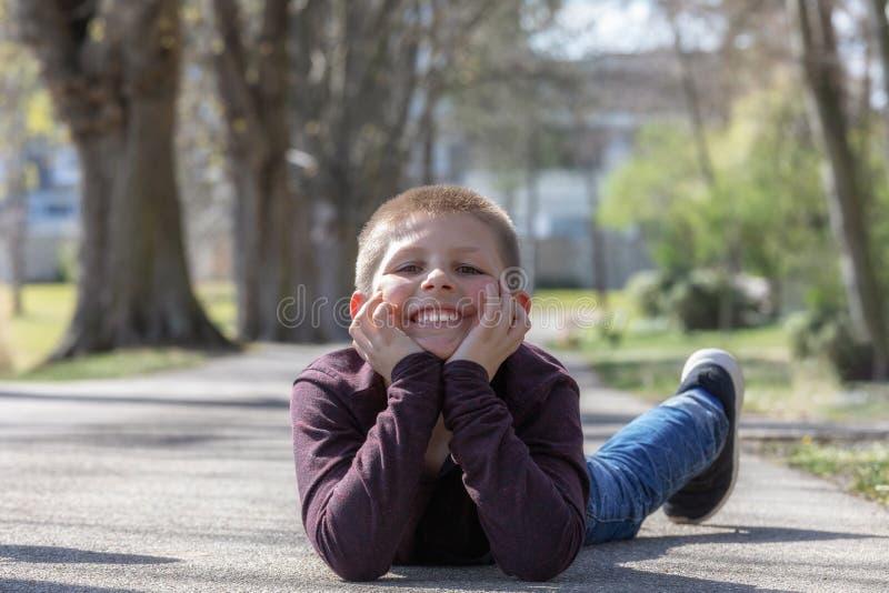 Gulligt litet barn, blond litet barnpojke som spelar utomhus att ligga på gatan royaltyfria foton
