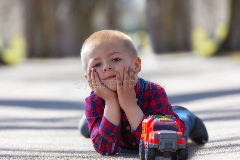 Gulligt litet barn, blond litet barnpojke som spelar utomhus att ligga på gatan arkivfoton