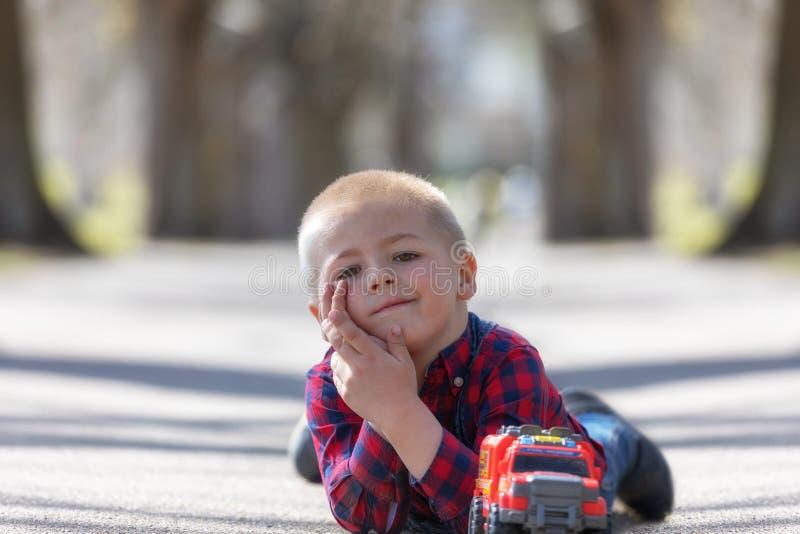 Gulligt litet barn, blond litet barnpojke som spelar utomhus att ligga på gatan royaltyfria bilder