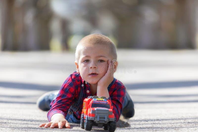 Gulligt litet barn, blond litet barnpojke som spelar utomhus att ligga p? gatan royaltyfri fotografi