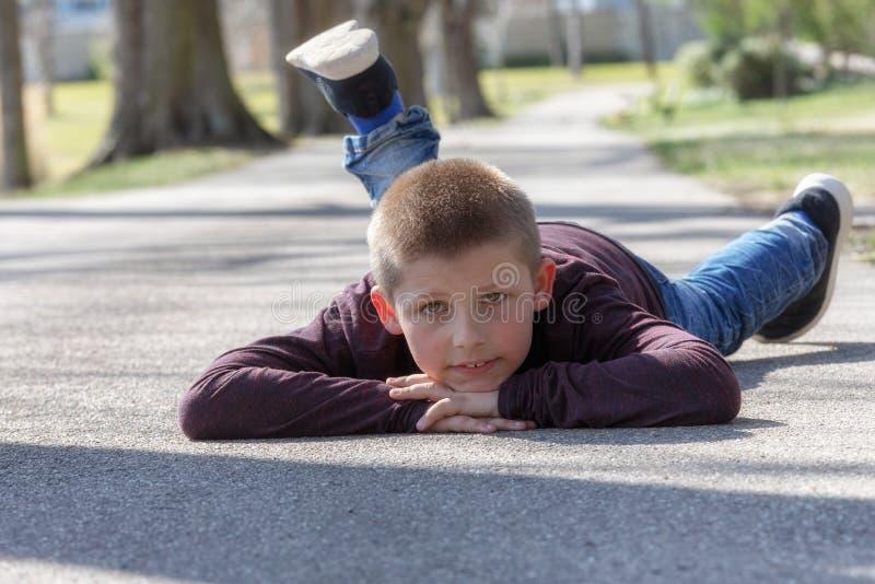 Gulligt litet barn, blond litet barnpojke som spelar utomhus att ligga p? gatan arkivbilder