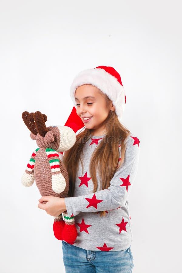 Gulligt litet barn i jultomtenhatt med stack leksakhjortar Flickan som skrattar och tycker om gåvan Julfilial och klockor arkivfoto