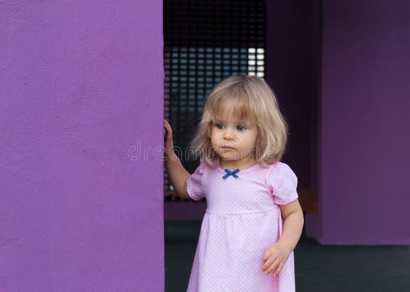Gulligt litet barn i rosa sommarklänning i åriga ärtor 1 utomhus bort se Barndom Stående av den allvarliga och härliga blondinen royaltyfri foto