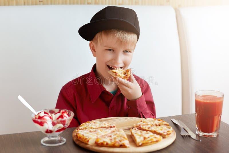 Gulligt litet barn i stilfull kläder som äter pizza och glass som dricker tomatfruktsaft, medan placera i kafé Lyckligt barn som  arkivbilder