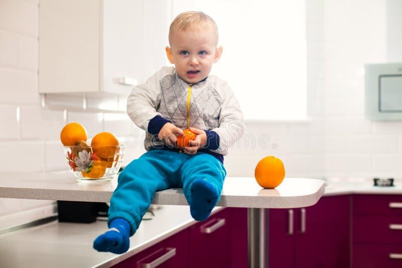 Gulligt litet barn med frukter i k?k royaltyfria bilder