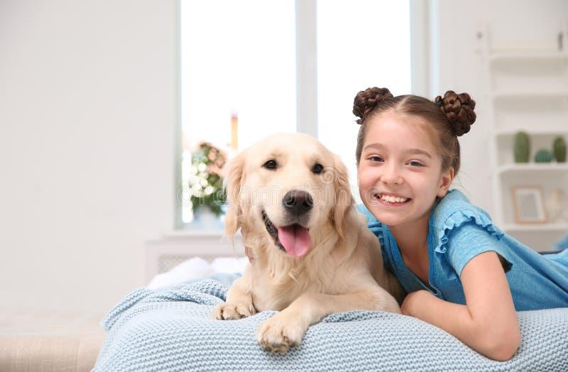 Gulligt litet barn med hennes husdjur på säng royaltyfri bild