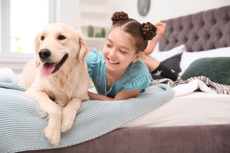 Gulligt litet barn med hennes husdjur på säng arkivfoton