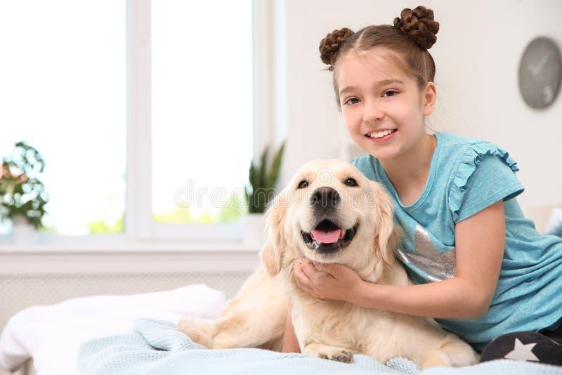 Gulligt litet barn med hennes husdjur på säng royaltyfri foto