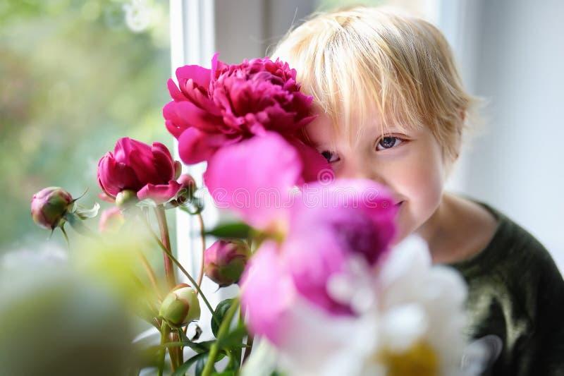 Gulligt litet barn och fantastisk bukett av vita och purpurfärgade pioner royaltyfri foto