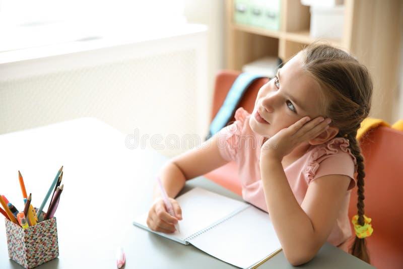 Gulligt litet barn som dagdrömmer på skrivbordet i klassrum arkivbild