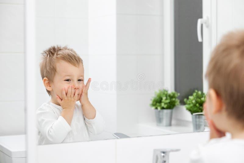 Gulligt litet barn som lär hur man tvättar hans framsida arkivfoton