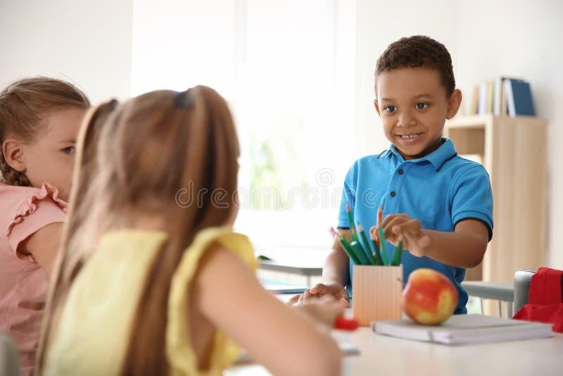 Gulligt litet barn som tar hans blyertspenna för klasskompis` s arkivbild