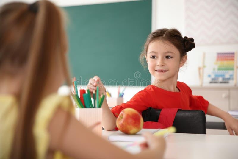 Gulligt litet barn som tar hennes blyertspenna för klasskompis` s royaltyfria bilder
