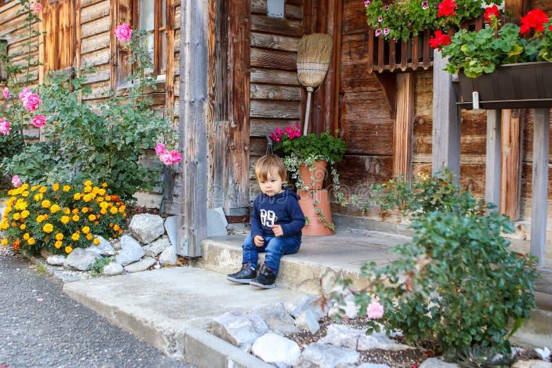 Gulligt litet fundersamt pojkesammanträde på den främre farstubron av trähuset för gammal tappning som omges av blommor arkivfoto