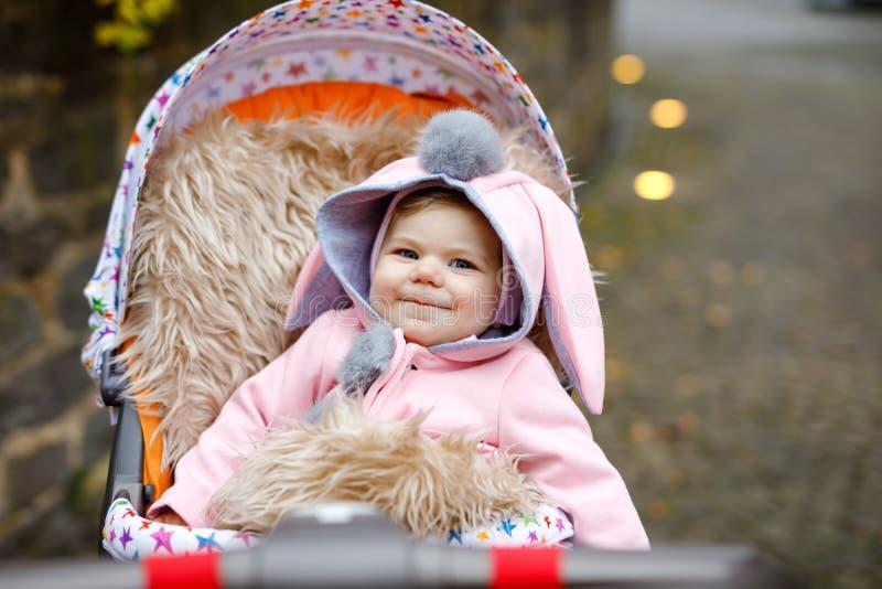Gulligt litet h?rligt behandla som ett barn flickasammantr?de i pramen eller sittvagnen p? h?stdag Lyckligt le barn i varm kl?der royaltyfri fotografi