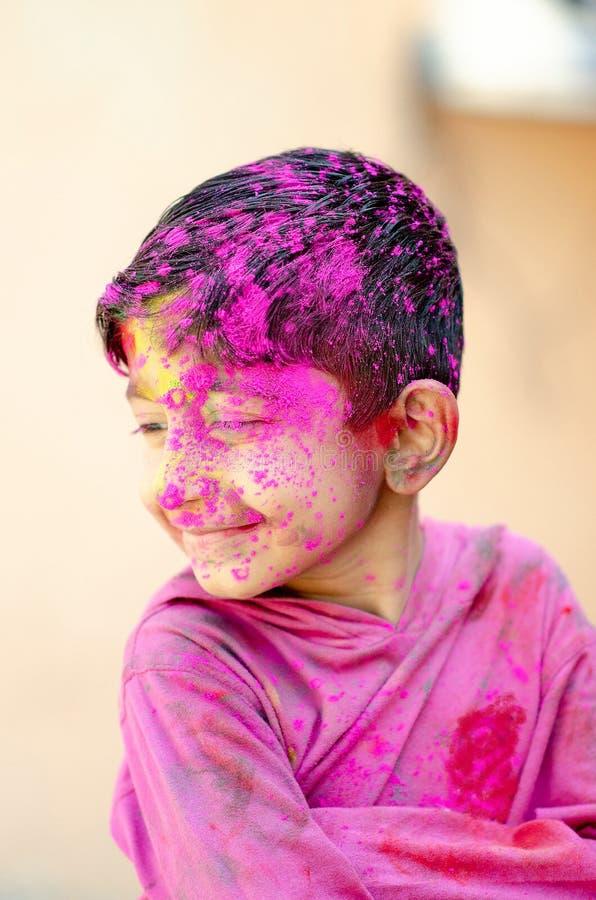 Gulligt litet indiskt pojkebarn med färgad färg för framsidamålarfärgpoweder som kastas på hans framsida under den indiska festiv royaltyfri fotografi