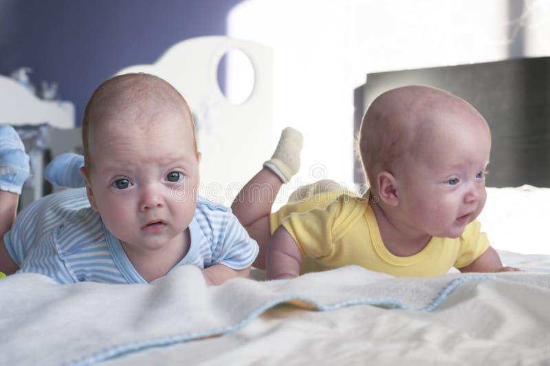 Gulligt litet kopplar samman behandla som ett barn pojken, och flickan ligger på sängen och lär att rymma deras huvud royaltyfri foto