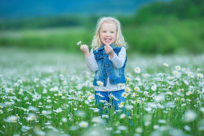 Gulligt litet le behandla som ett barn flickan i litet blont barn för kamomillfält med kransen på huvudet i kamomillar som bär je arkivfoto