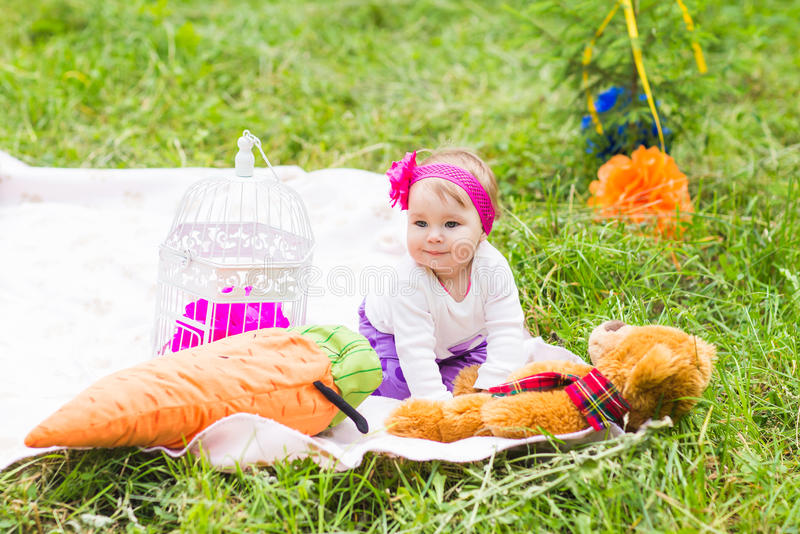 Gulligt litet lyckligt behandla som ett barn flickan med den stora bruna nallebjörnen på äng för grönt gräs, våren eller sommarsä arkivbild