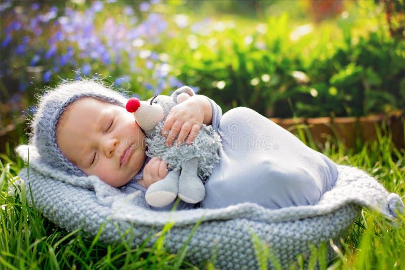 Gulligt litet nyfött behandla som ett barn pojken, att sova som rymmer gulligt litet mous arkivfoton