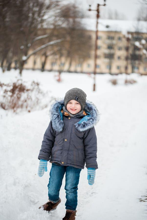 Gulligt litet roligt barn i färgrik vinterkläder som har gyckel med snö, utomhus under snöfall Aktiv det friafritid med ch royaltyfri fotografi