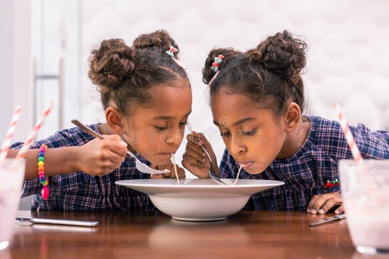 Gulligt litet syskon som äter deras lunch i kafeteria efter dagis arkivbild