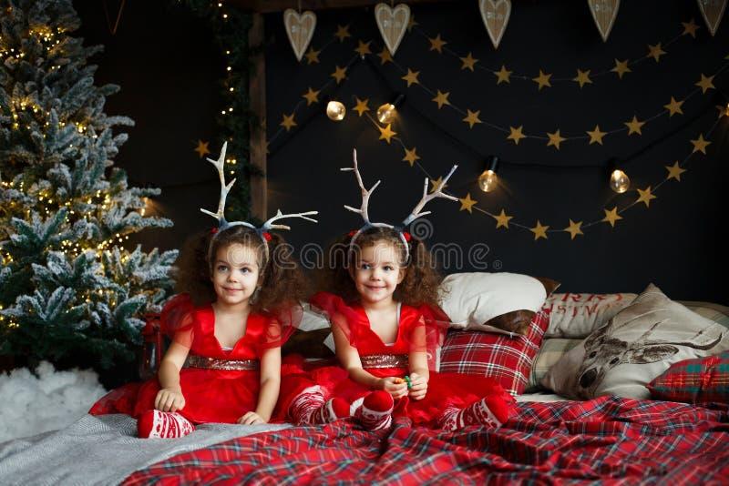 Gulligt lockigt kopplar samman flickan som sitter på sängen i dekorerat xmas-rum, på julaftonen 2018 nära granträd för nytt år me arkivbild