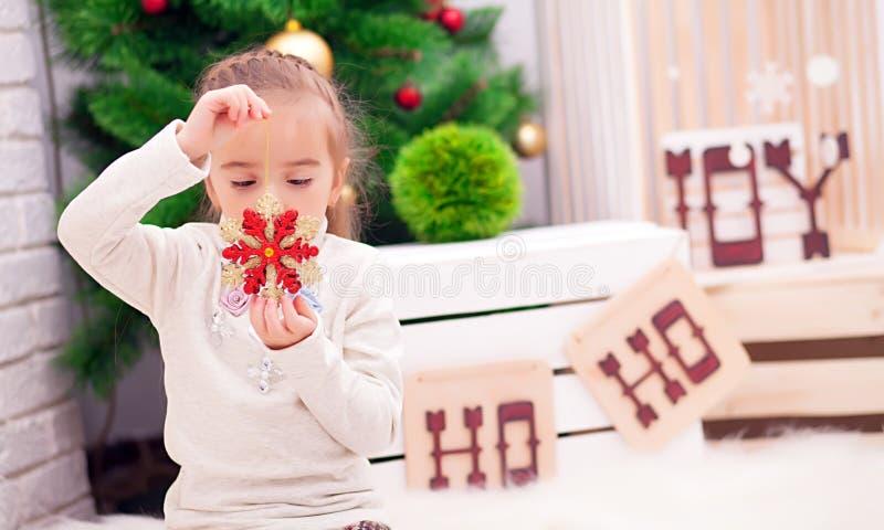 Gulligt lockigt litet barnflickaanseende på en julmatställetabell som sätter disken som förbereder sig att fira Xmas-helgdagsafto arkivfoto