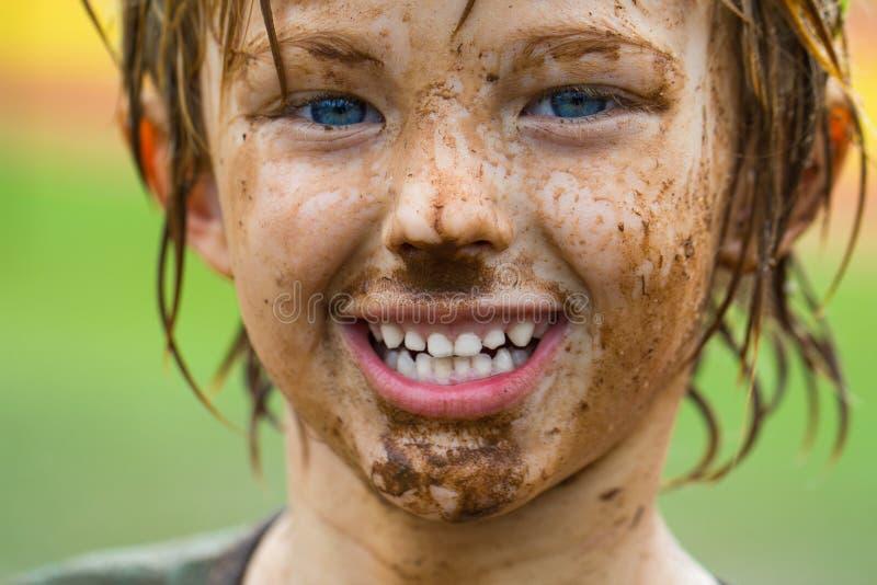 Gulligt lyckligt barn med den smutsiga framsidan, når att ha spelat royaltyfria bilder