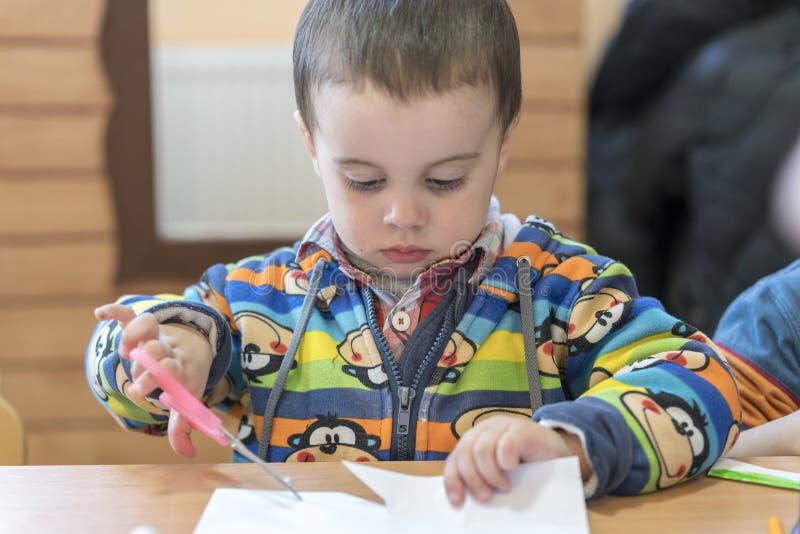 Gulligt lyckligt behandla som ett barn pojkeungebarnet som spelar och klipper färgrikt papper med sax Gullig pys med hår för mörk arkivfoto