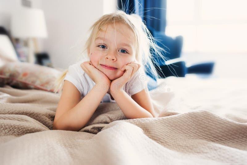 Gulligt lyckligt litet barnflickasammanträde på säng i pajama leka för barnutgångspunkt royaltyfri foto