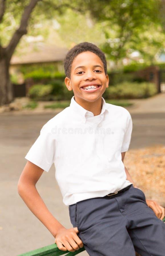 Gulligt lyckligt svart pojkesammanträde på porten royaltyfria foton