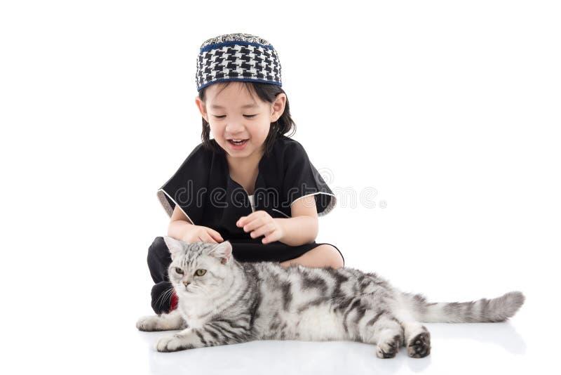 Gulligt muslimbarn som spelar med strimmig kattkatten royaltyfri foto