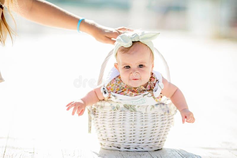 Gulligt mycket litet nyfött behandla som ett barn prinsessan i en balettkjol med en pilbåge på en korg med plädet slappa signaler royaltyfri fotografi