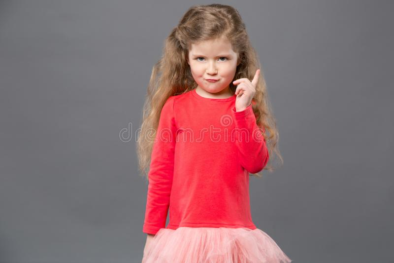 Gulligt nätt flickaanseende mot grå bakgrund royaltyfri fotografi