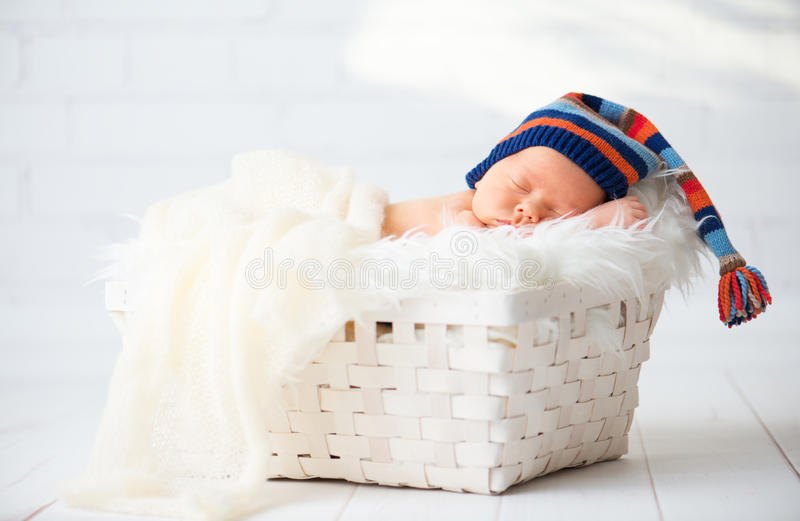 Gulligt nyfött behandla som ett barn i den blåa toppluvan som sover i korg royaltyfri bild