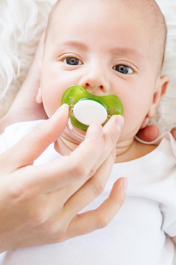 Gulligt nyfött behandla som ett barn med en fredsmäklare royaltyfri bild