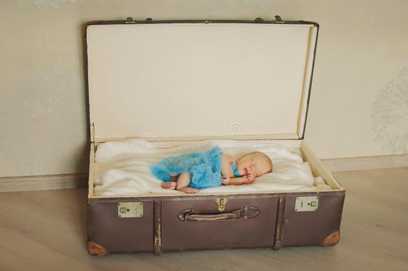 Gulligt nyfött behandla som ett barn sover i en gorzontal resväska arkivbild
