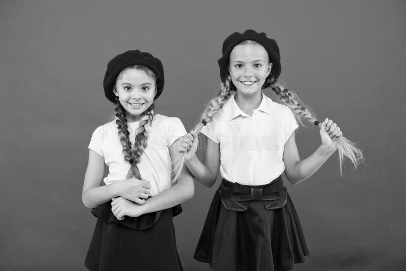 Gulligt och stilfullt Sm? ungar som b?r stilfulla franska basker Franska stilflickor Gulliga flickor som har den samma frisyren royaltyfri fotografi